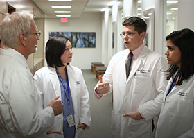 Regis O'Keefe, MD, PhD, and orthopaedic surgery residents talking in the hallway